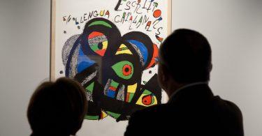 Imagem de pessoas olhando uma obra de Joan Miró