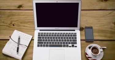 Mesa de trabalho com notebook, café, caderno e celular
