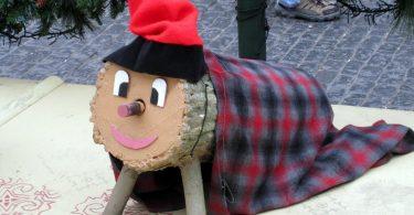 Imagem de tronco de madeira com manta e gorro vermelho