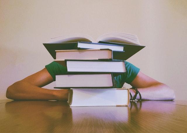 Aluna atrás de uma pilha de livros