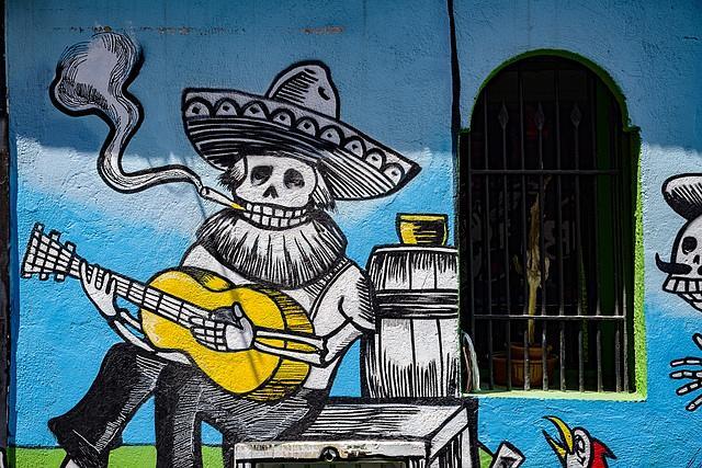 Grafite de uma caveira tocando violão