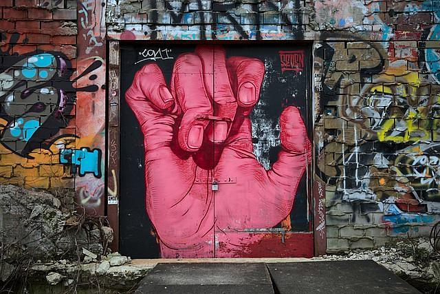 Grafite de uma mão vermelha quase fechada