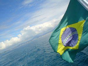 Imagem de bandeira do Brasil com o mar ao fundo