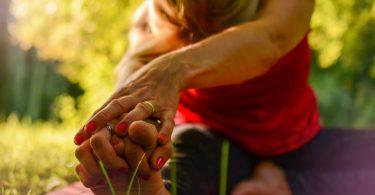 Imagem de mulher praticando ioga ao ar livre