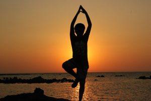 Imagem de pessoa praticando ioga na praia