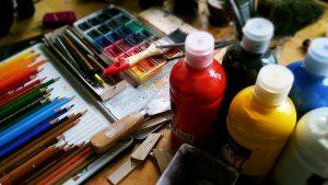 Imagem de lápis de cor, tinhas e papel sobre mesa