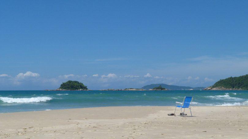 Imagem de praia vazia e céu limpo