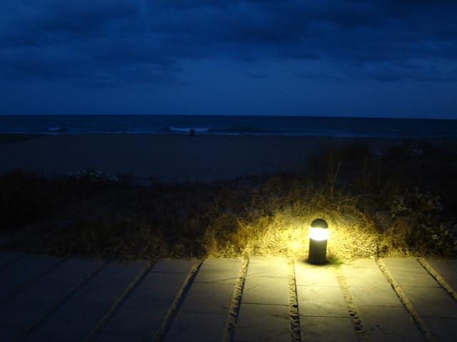 Calçada de madeira na praia iluminada