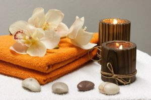 Imagem de pétalas sobre toalha, velas e pedras brancas