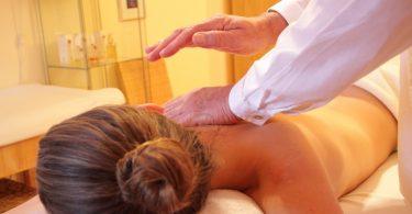 Imagem de mulher deitada de costas, recebendo massagem