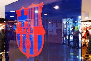 Imagem de porta de vidro com escudo do FC Barcelona