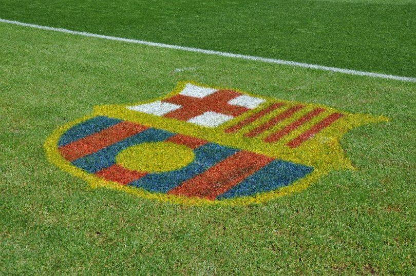 Imagem de escudo do FC Barcelona no gramado