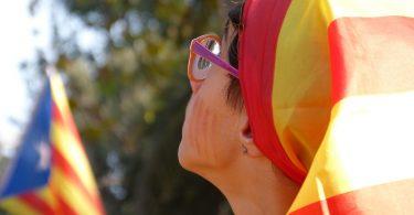Imagem de mulher com bandeira da Catalunha na cabeça
