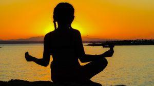 Imagem de mulher meditando na praia