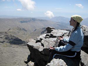 Imagem de mulher praticando meditação na montanha