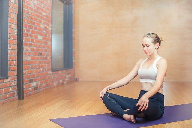 Mulher com as pernas cruzadas meditando
