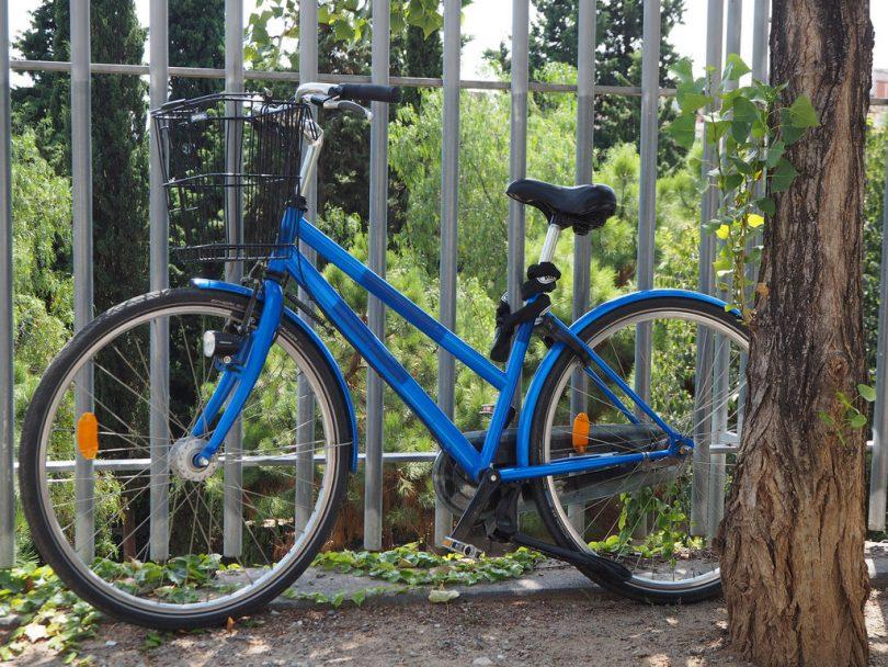 Imagem de uma bicicleta azul encostada em grades