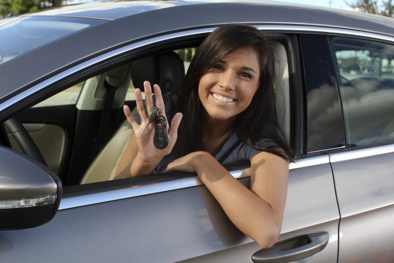 Imagem de mulher no carro com chave na mão