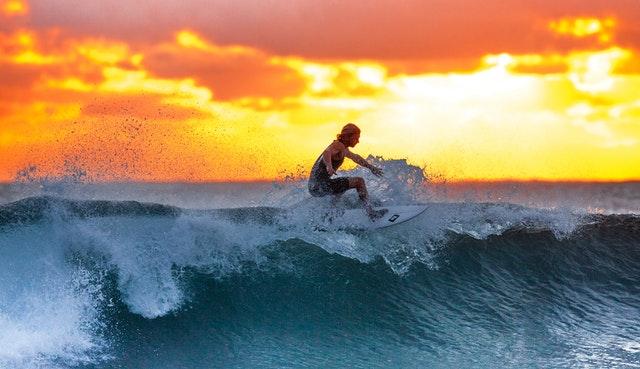 Sufista tentando dominar o curso de uma onda na praia