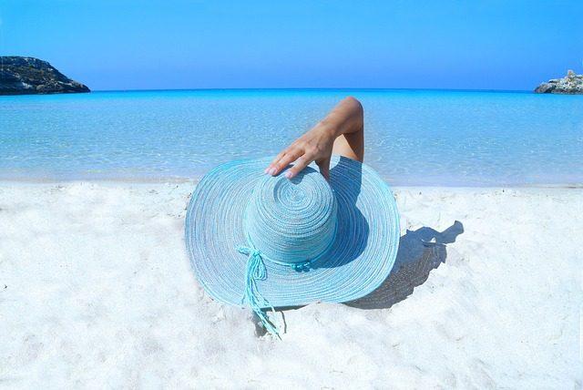 Imagem de mulher deitada na areia da praia