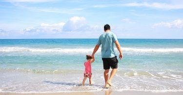 Imagem de pai e filha andando na praia