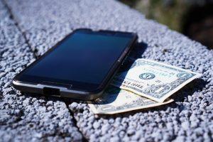 Imagem de celular ao lado de dinheiro
