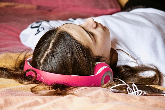 Menina escuta áudiolivro deitada na cama