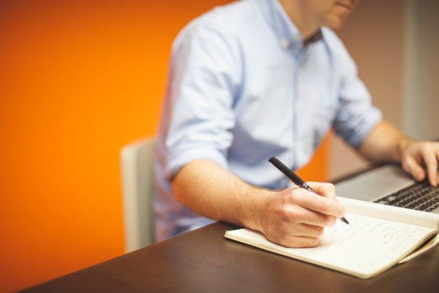 Homem fazendo anotações diante de um computador