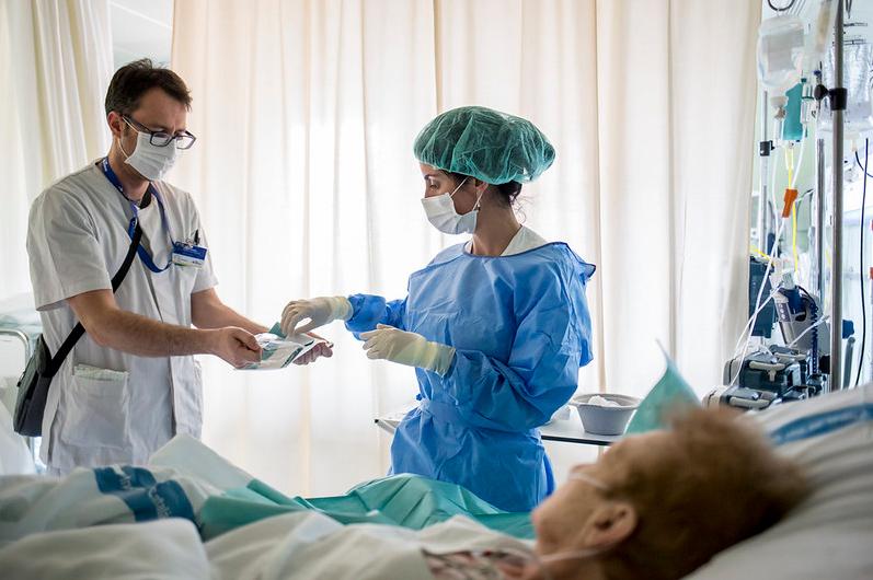 Médicos em uma sala de clínica, próximos a uma paciente deitada na cama