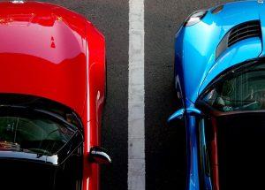 Imagem de carro vermelho e carro azul brilhantes um ao lado do outro em estacionamento