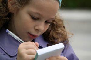 Imagem de garota escrevendo em um bloco de anotações