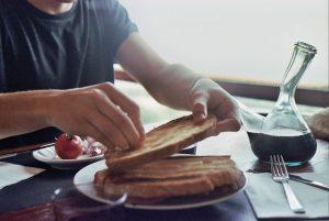 Imagem de homem passando tomate pra fazer pa amb tomàquet