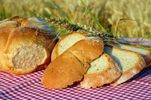 Imagem de lascas grossas de pão sobre toalha de mesa ao ar livre
