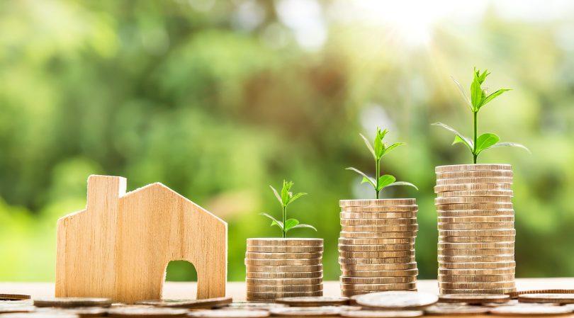 Imagem de miniatura de casa ao lado de moedas