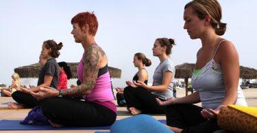 Imagem de mulheres praticando ioga ao ar livre