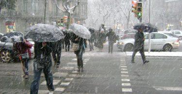 Imagem de pessoas atravessando rua sob neve