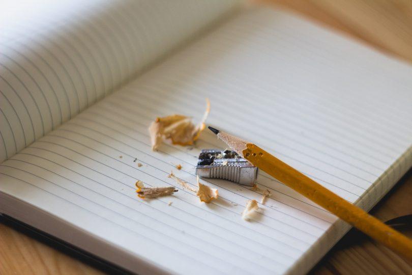 Imagem de um lápis com apontador sobre caderno