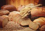 Imagens de vários tipos de pão e trigo sobre mesa de madeira