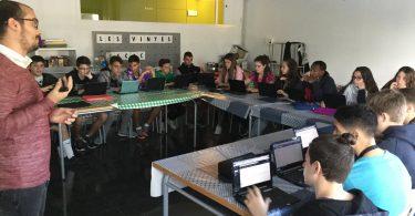 Imagem de alunos com pequenos computadores à frente sobre mesas