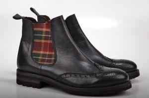 Imagem de botas pretas com uma parte em xadrez colorido