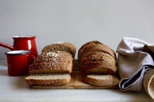 Imagem de pão de massa madre sobre mesa com bule de café e toalha