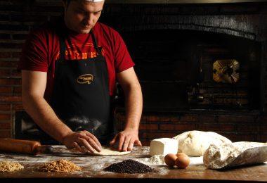 Imagem de padeiro mexendo em massa de pão
