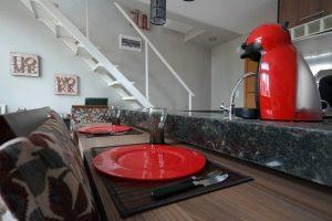 Imagem de mesa com pratos vermelhos em uma cozinha