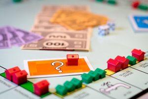 Imagem de pequenas casas com cédulas de dinheiro sobre tabuleiro de jogo