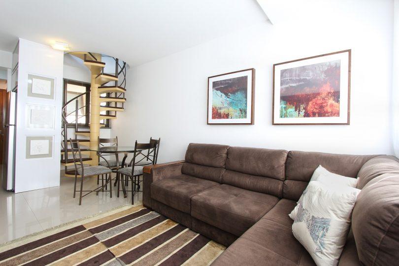 Imagem de sofá em sala com escada ao fundo