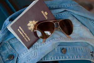 Imagem de óculos de sol, jaqueta e um passaporte
