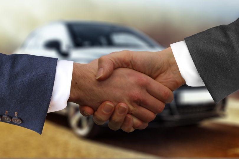 Imagem de dois homens apertando as mãos diante de um carro