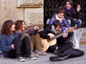 Imagem de jovens sentados em uma calçada em Barcelona