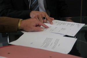Imagem de pessoas analisando um contrato