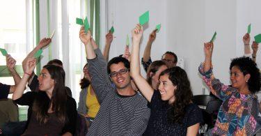 Imagem de pessoas votando em reunião